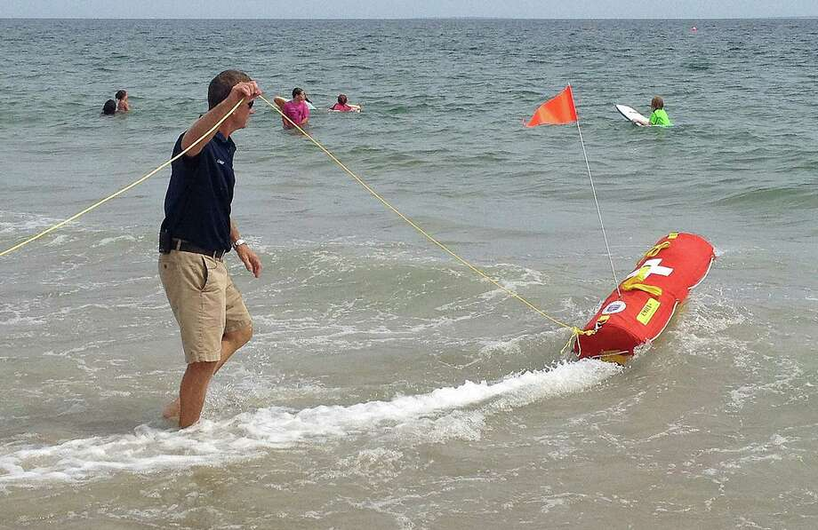 In this Wednesday, Aug, 8, 2012 photo, Misquamicut, R.I., Fire Chief Louis Misto, left, holds a line attached to the EMILY remote-control lifesaving device as it propels itself in the water and away from the shore at Old Town Beach, in Westerly, R.I. EMILY, an acronym for Emergency Integrated Lifesaving Lanyard, is a small watercraft fitted with a flotation device and can go up to 22 mph, allowing it to get to people more quickly, and in some cases more safely, than any human. (AP Photo/Michelle R. Smith) Photo: Michelle R. Smith