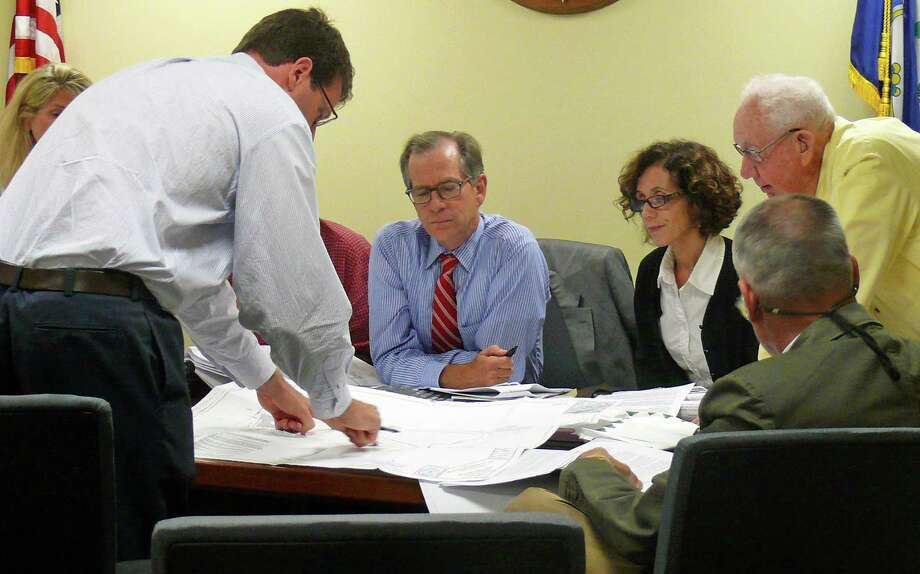Craig Flaherty, standing, from Redniss & Meade, reviews proposed changes to the Fairfield Metro project with the Inland Wetlands Commission members. Photo: Genevieve Reilly / Fairfield Citizen