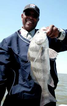 Kenny Houston shows off a black drum he caught while fishing with fellow...