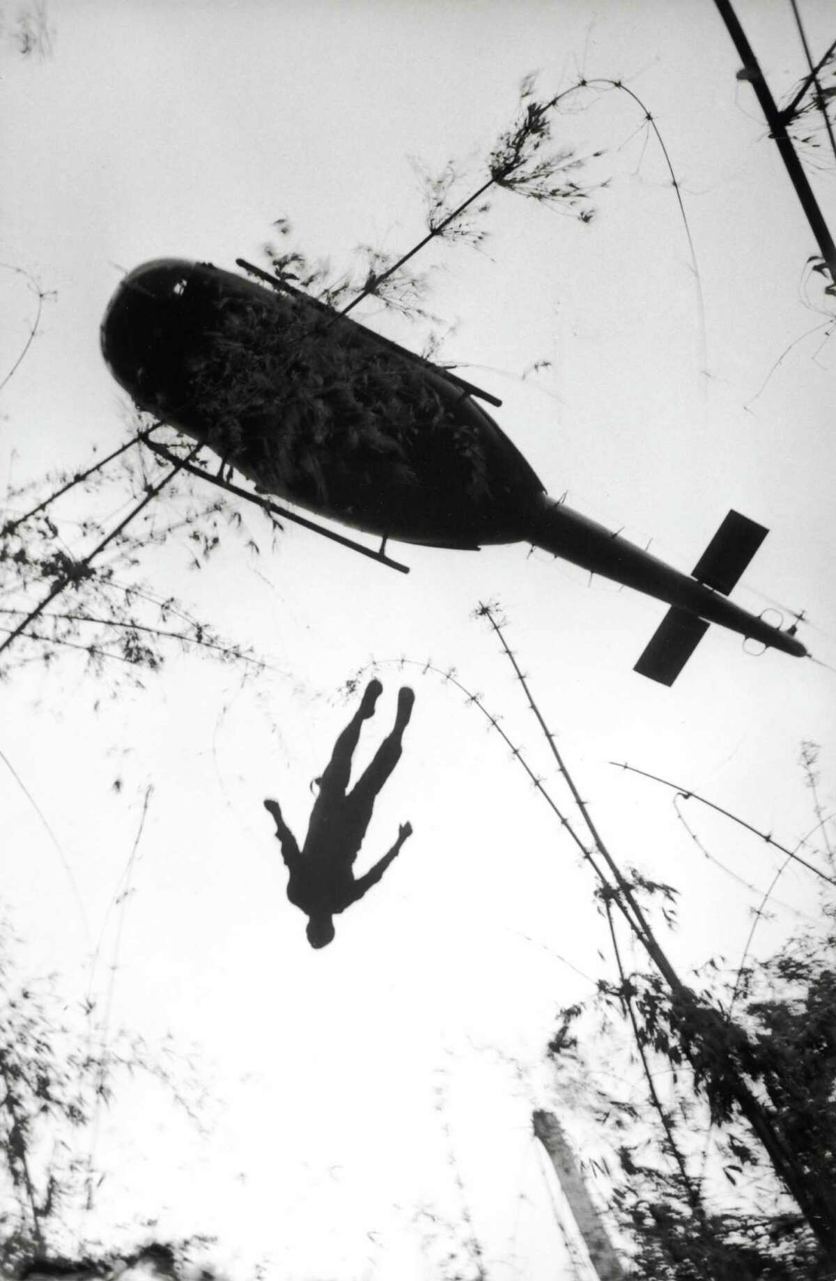 """From """"WAR/PHOTOGRAPHY: Photographs of Armed Conflict and Its Aftermath"""", at the Museum of Fine Arts, Houston Nov. 11 - Feb. 3: Henri Huet, French, 1927-1971 The body of an American paratrooper killed in action in the jungle near the Cambodian border is raised up to an evacuation helicopter, Vietnam 1966 Gelatin silver print, printed 2004 The Museum of Fine Arts, Houston, museum purchase AP/Wide World Photos"""