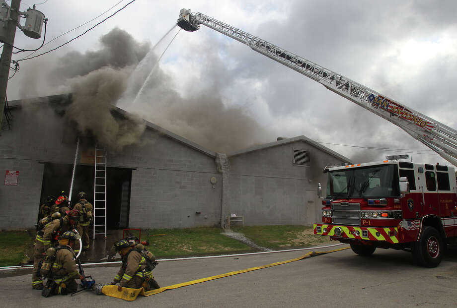 "San Antonio firefighters battle a smoky two-alarm warehouse fire Friday May 31, 2013 at 307 Indiana on San Antonio's East Side. San Antonio fire chief Charles Hood said the fire broke out about 9:40 a.m. and arriving firefighters found flames shooting through the roof of Lonestar Tooling Solutions. Hood said the 15 people in the building were evacuated and no firefighters were injured during the blaze. Hood said the building contained numerous chemicals and oxygen and acetylene tanks. ""It was a defensive fire from the start,"" Hood said. The cause of the blaze is being investigated. Photo: JOHN DAVENPORT, SAN ANTONIO EXPRESS-NEWS / ©San Antonio Express-News/Photo may be sold to the public"
