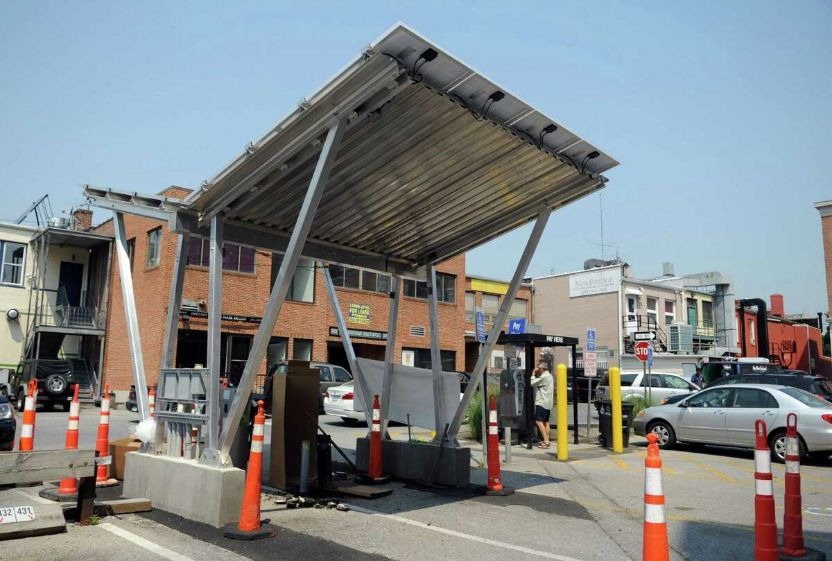 Jerry Petrizzi, Project Manager at American Solar and Alternative Power, works to finish installing a GE unit at the new solar-powered electric vehicle charging station at the Bedford Street municipal parking lot in Stamford on Friday, August 17, 2012. Use of the station will initially be free, and solar power generated but not used by electric cars will be sold back to Connecticut Light & Power at the retail rate.