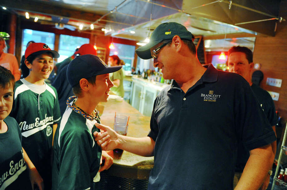 Frank Polley, 12, and his dad Owen, hang out at a party for the New England team after its first game, which was held at the Bullfrog Brewery in downtown Williamsport, Penn. on Thursday August 16, 2012. Frank is a player on the Fairfield National team and the team came out to support Fairfield American in its trip to the series. At left is Franks teammates John McMillan, with cap, and Gus Bochanis. Photo: Christian Abraham / Connecticut Post