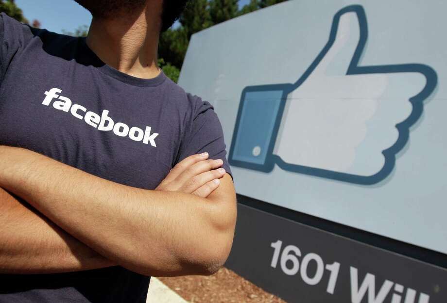 A Facebook worker waits for friends to arrive outside of Facebook headquarters in Menlo Park, Calif., Friday, Aug. 17, 2012. Facebook'sstock has come a penny short of hitting $19 for the first time, meaning it has nearly lost half of its market value since its public offering in May. (AP Photo/Paul Sakuma) Photo: Paul Sakuma / AP