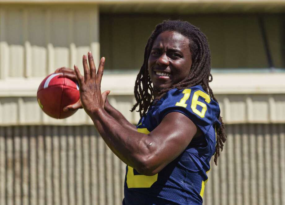 Michigan quarterback Denard Robinson throws passes for photographers during the NCAA college football team's annual media day on Sunday in Ann Arbor, Mich. (AP Photo/Tony Ding) Photo: Tony Ding, Associated Press / FR143848 AP