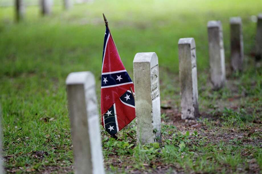 A confederate flag is seen at a tombstone on the cemetery at  Beauvoir House, Jefferson Davis' historic home, in Biloxi, Miss., Thursday, Aug. 16, 2012.  Commemorating the 150th anniversary of the Civil War can be an angst-filled task in Mississippi, with its long history of racial strife and a state flag that still bears the Confederate battle emblem. Well-intentioned Mississippians who work for racial reconciliation say slavery was morally indefensible. Still, some speak in hushed tones as they confess a certain admiration for the valor of Confederate troops who fought for what was, to them, the hallowed ground of home and country. (AP Photo/Gerald Herbert) Photo: Gerald Herbert, Associated Press / AP