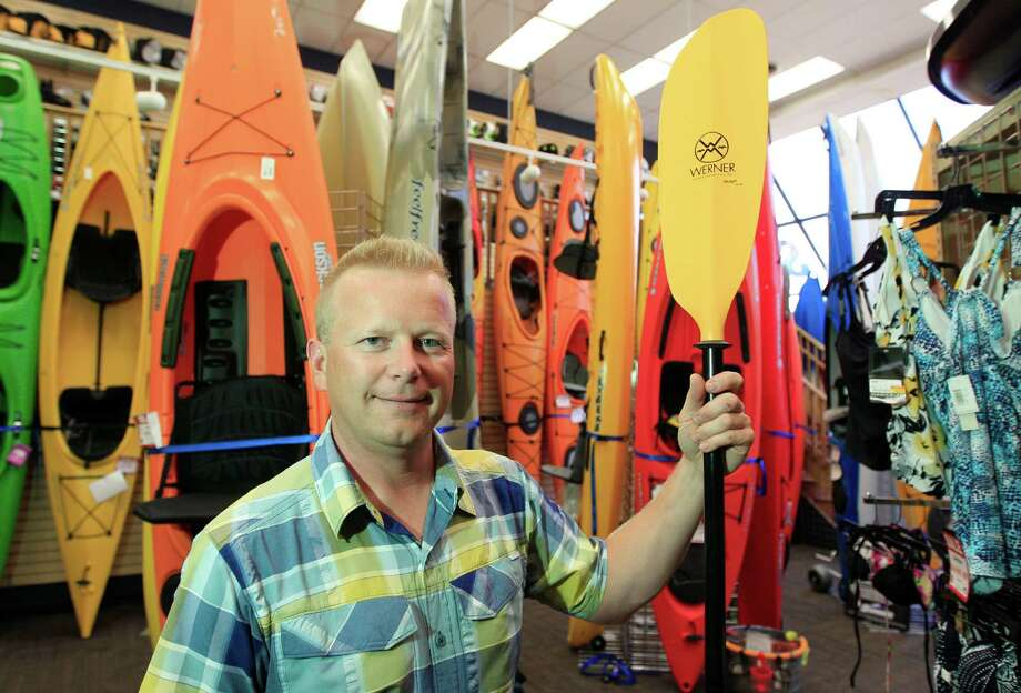 In a photo from Tuesday, Aug. 7, 2012, Andy Schepper, vice president of Summit Sports in Keego Harbor, Mich., stands next to kayaks his company sells.  With plants shriveling up and outdoorsy types feeling it's too hot to be active in the extreme summer heat, many small business owners with seasonal businesses aren't ringing up a lot of sales. (AP Photo/Carlos Osorio) Photo: Carlos Osorio / AP