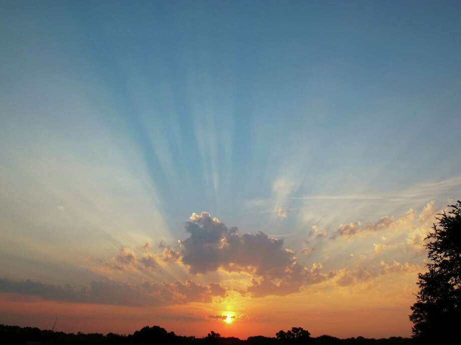 These crepuscular rays were formed by sunlight projected between clouds in a smoky Texas sky at sunset. Photo: Forrest M. Mims III, For The Express-News
