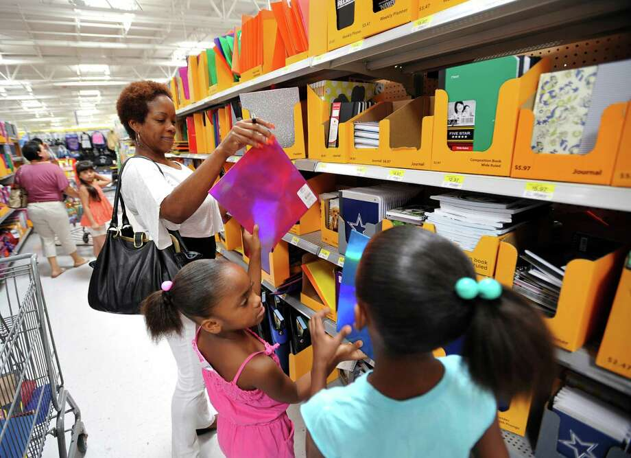 At the Walmart on N. Twin City Highway, Naomi Bailey, left, and her two daughters Tiana, center, and Zyara, right, shop for school supplies. The girls will be starting second grade in Port Arthur. Friday morning started the 2012 annual tax free weekend that runs through Sunday.  Texans will save 8.25 percent in state and local taxes this weekend when buying qualifying clothing, backpacks and school supplies.  Dave Ryan/The Enterprise