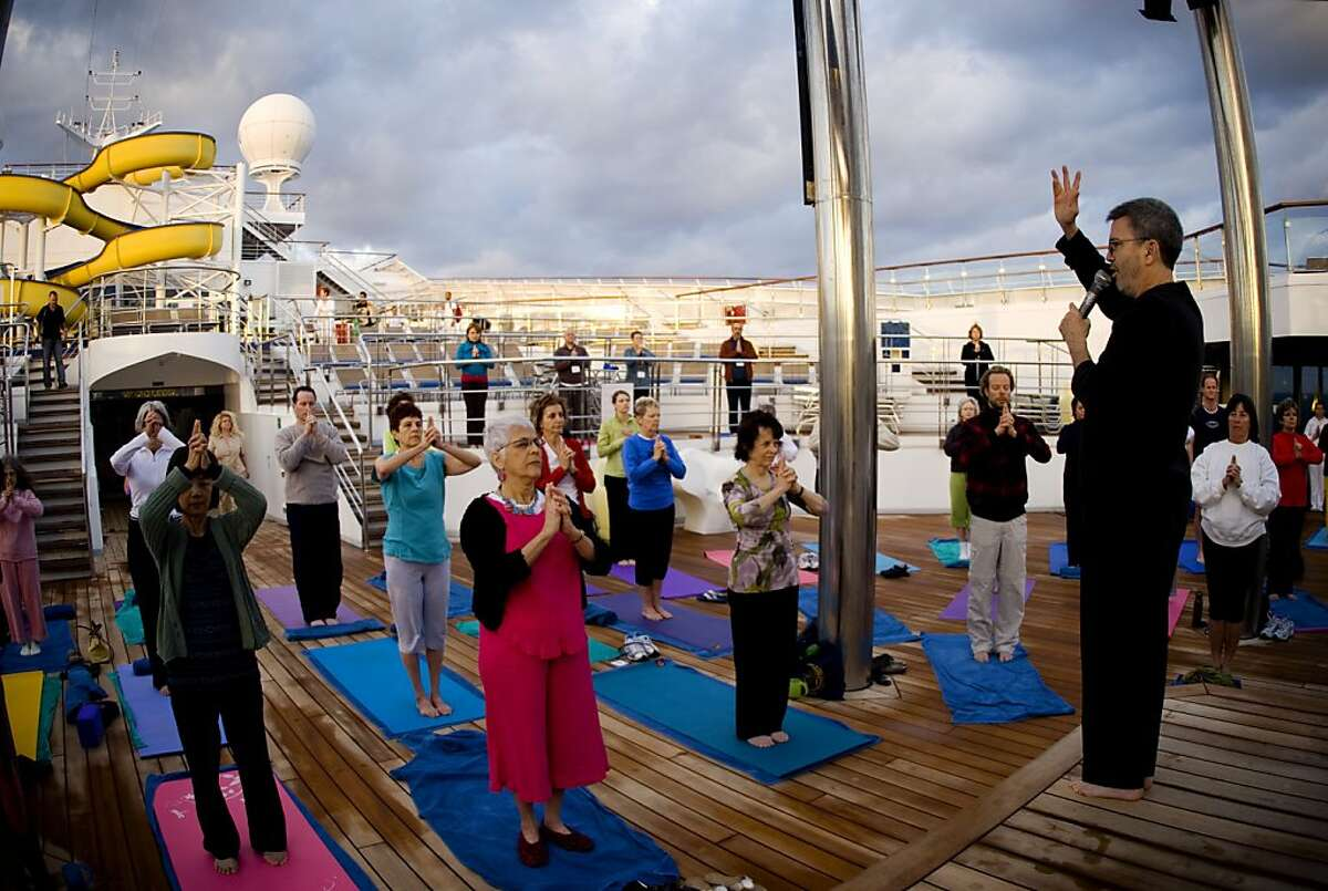 Passengers doing yoga on deck during the annual Holistic Holiday at Sea, one of a growing number of health-themed cruises.