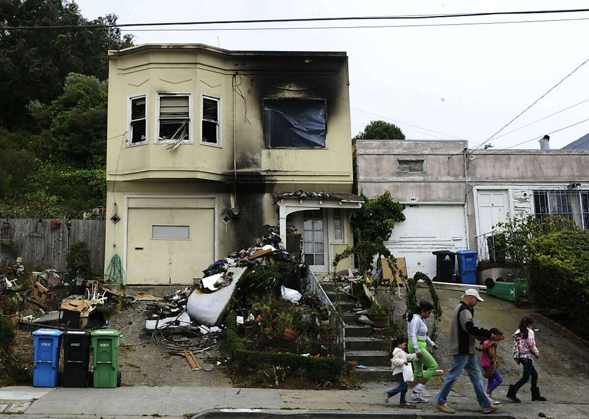 The Arciga Duenas family walks past the house that has been in fire on Friday, Aug 17, 2012 in San Francisco, Calif.