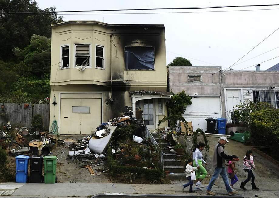 The Arciga Duenas family walks past the severely damaged home where two men had died in Friday morning's fire. Photo: Yue Wu, The Chronicle
