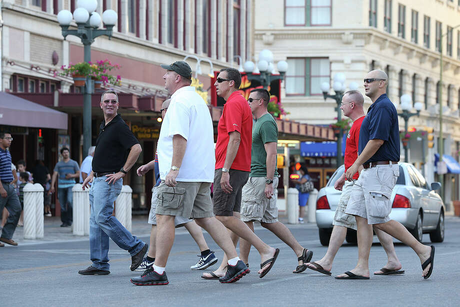 A group of men gather in the scene as tourists visit Alamo Plaza on August 5, 2014. Photo: TOM REEL, San Antonio Express-News / San Antonio Express-News