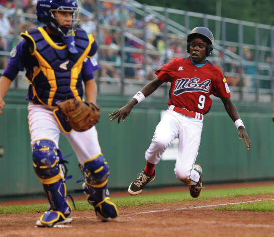 Uganda's #9 Felix Enzama starts his slide into home plate as Latin America catcher Juan Crisp waits for the ball, at the Little Leauge World Series in South Williamsport, Penn. on Friday August 17, 2012. Photo: Christian Abraham / Connecticut Post