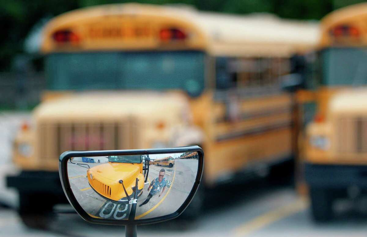 Phil Felton, reflected Friday in a bus mirror, is director of Alief ISD's Transportation Center. Like other area districts, Alief is having trouble hiring enough bus drivers and still has 10 routes to fill before school starts.