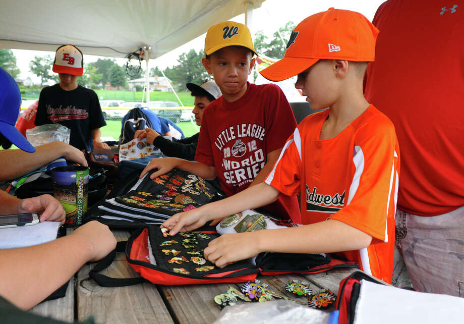 Kyler Alexander, 10, of South Williamsport, and Moxem Cotter, 8, in front, of Williamsport, do a little pin trading at the Little Leauge World Series in South Williamsport, Penn. on Friday August 17, 2012. Photo: Christian Abraham / Connecticut Post