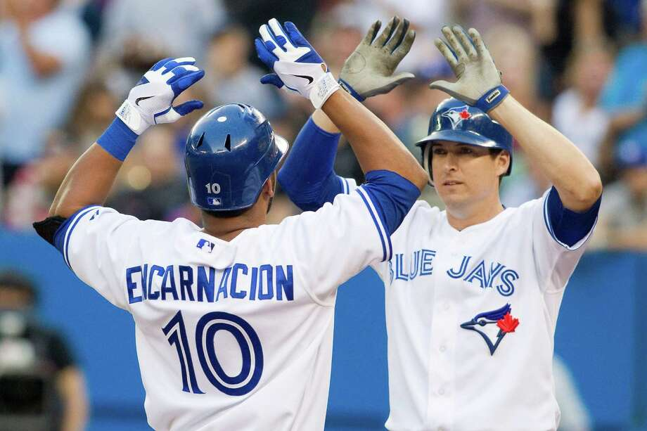 Toronto Blue Jays' Kelly Johnson, right, congratulates teammate Edwin Encarnacion for hitting a two-run home run off Texas Rangers starting pitcher Yu Darvish during the first inning of baseball game action in Toronto, Friday, Aug. 17 , 2012. Photo: The Canadian Press, Chris Young