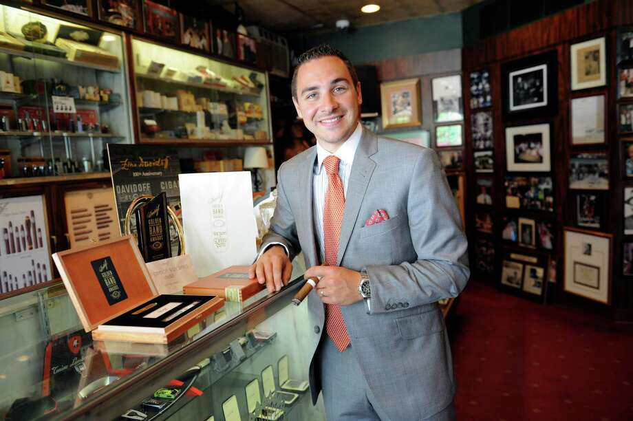 T. Michael Cafagno, owner of the Tobacconist of Greenwich LTD won a national award called the Golden Band Davidoff Best Performance Award. Cafagno stands with his award Thursday, Aug. 16, 2012.. Photo: Helen Neafsey / Greenwich Time