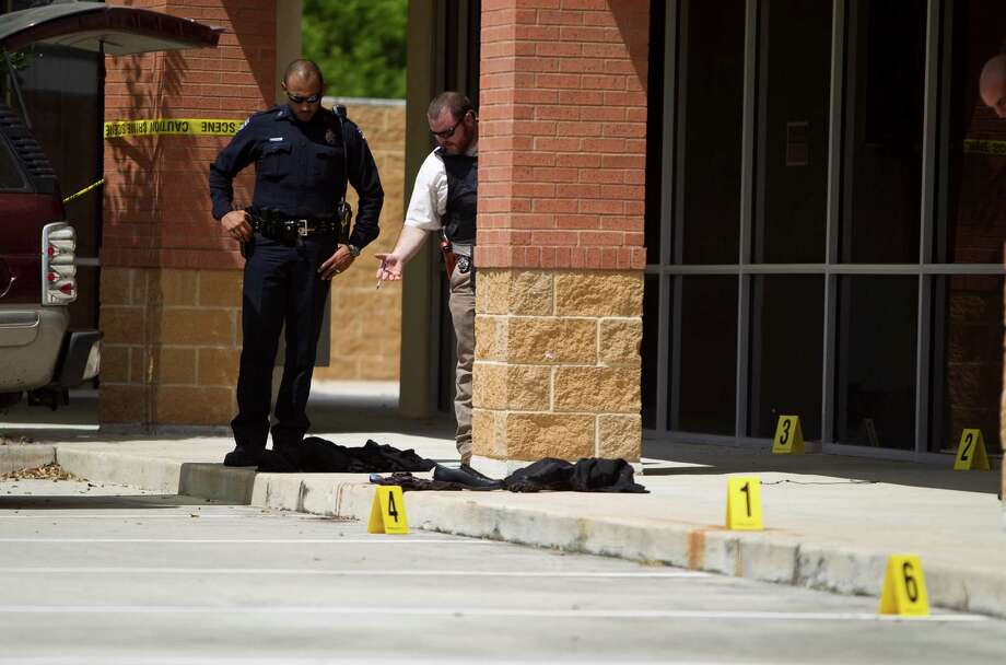 Pearland police officers inspect the scene where a man was shot on Friday. A Houston officer spotted the suspect, who had a mask and shotgun, near Capital Bank. He then summoned Pearland officers to the scene. Photo: Nick De La Torre / © 2012  Houston Chronicle