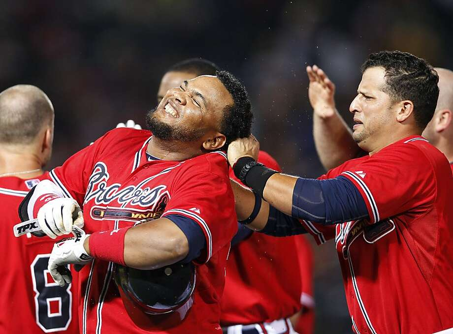 Atlanta Braves pinch hitter Juan Francisco, left, celebrates with teammate Martin Prado after driving in the game-winning run with a base hit in the 11th inning. Photo: John Bazemore, Associated Press