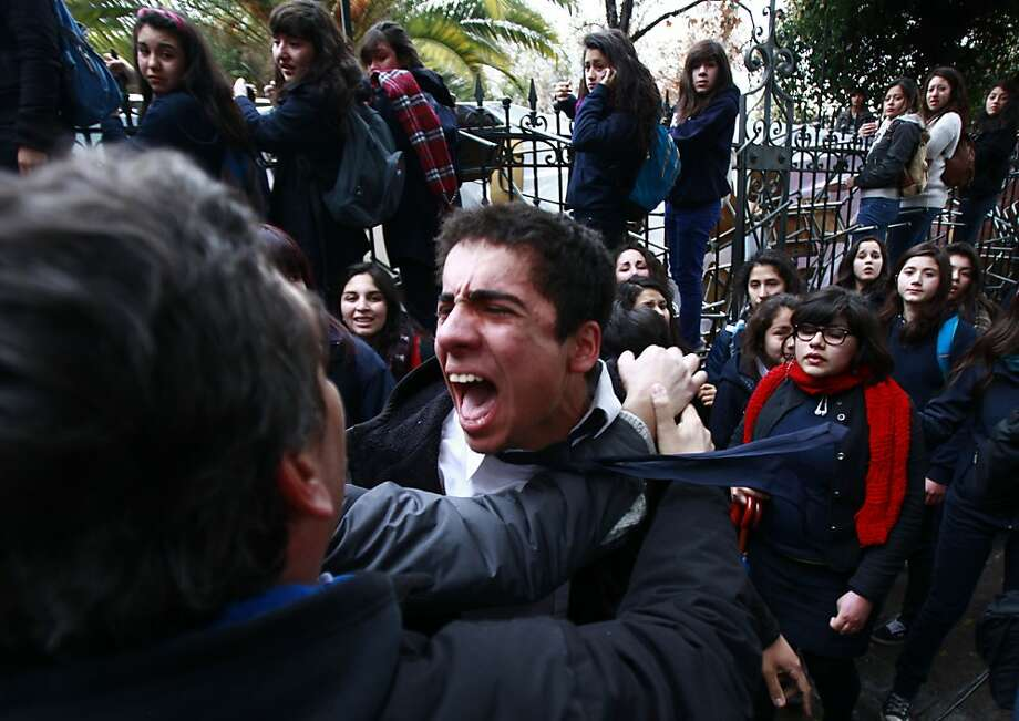 People try to calm a student who watched his friends get arrested by police as they were evicted from their all-girls high school, Liceo Carmela Carvajal, which students occupied to demand education reform in Santiago,  Chile, Friday, Aug. 17, 2012.  Protesters say the education system fails families with poor quality public schools, expensive private universities, unprepared teachers and banks that make education loans at high interest rates that most Chileans can ill afford. Photo: Luis Hidalgo, Associated Press