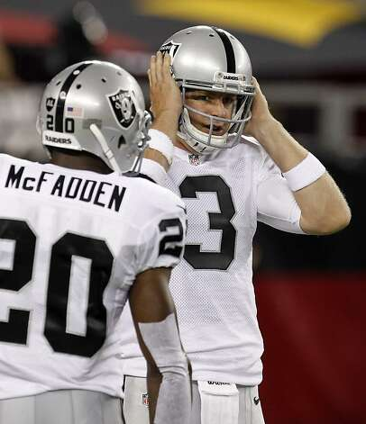 Oakland Raiders quarterback Carson Palmer talks with running back Darren McFadden in the first half of a preseason NFL football game against the Arizona Cardinals, Friday, Aug. 17, 2012, in Glendale, Ariz. (AP Photo/Ross D. Franklin) Photo: Ross D. Franklin, Associated Press
