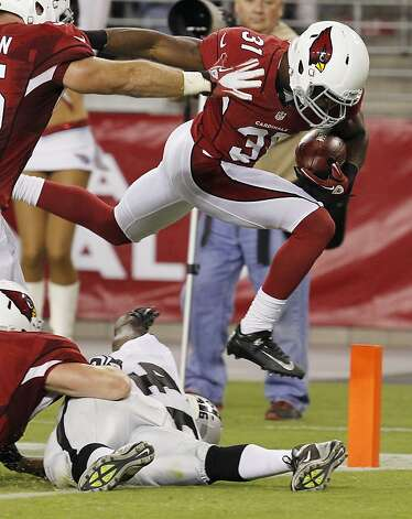 Arizona Cardinals' Justin Bethel (31) leaps over Oakland Raiders' Lonyae Miller and into the end zone for a touchdown after blocking a punt against the Oakland Raiders during the first half in a preseason NFL football game Friday, Aug. 17, 2012, in Glendale, Ariz. (AP Photo/Ross D. Franklin) Photo: Ross D. Franklin, Associated Press