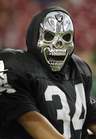 An Oakland Raiders fan watches his team warm up prior to a preseason NFL football game against the Arizona Cardinals, Friday, Aug. 17, 2012, in Glendale, Ariz. (AP Photo/Rick Scuteri) Photo: Rick Scuteri, Associated Press
