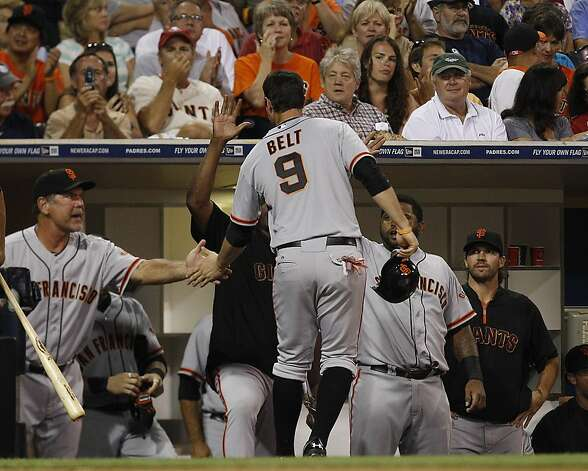 San Francisco Giants' Brandon Belt is greeted at the dugout by manager Bruce Bochy and teammates after scoring during the Giants' eight run third inning against the San Diego Padres  during in a baseball game Friday, Aug. 17, 2012 in San Diego. (AP Photo/Lenny Ignelzi) Photo: Lenny Ignelzi, Associated Press