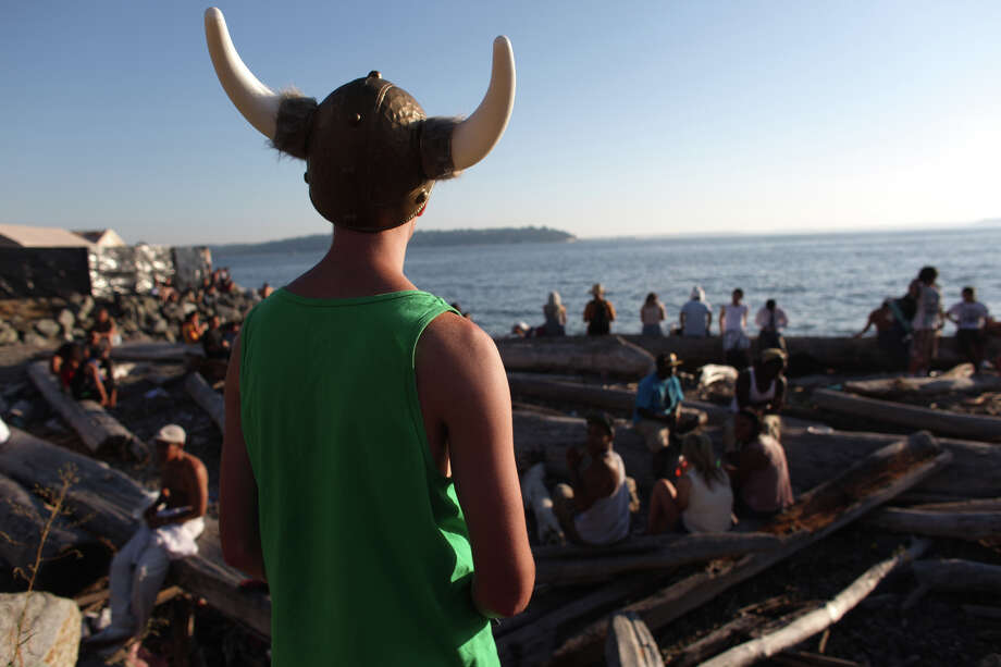 A participant looks at people gathered on driftwood during Seattle's Hempfest pro marijuana gathering at Myrtle Edwards Park on the Seattle waterfront on Friday, August 17, 2012. Hundreds of thousands of people are expected to attend the festival that lasts through the weekend. Photo: JOSHUA TRUJILLO / SEATTLEPI.COM