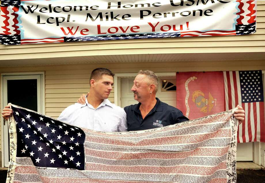 "Mike Perrone, 24, is welcomed home from serving in the armed forces in Afghanistan by his dad, Bill, at their Brookfield home Saturday, Aug. 18, 2012. Bill is working on the 9/11 site in New York City. They are holding a ""Flag of Honor"" with the names of everyone killed in the 9/11 disaster and signed by Bill's fellow union members and volunteer firefighters. He gave the flag to Mike to take to Afghanistan. Photo: Michael Duffy / The News-Times"