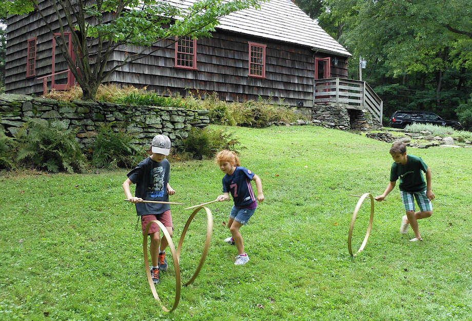 Children attending the History Camp sponsored by the Fairfield Museum and History Center roll wooden hoops on the grounds of the historic Ogden House, mimicking Colonial-era children's games. Photo: Mike Lauterborn / Fairfield Citizen contributed