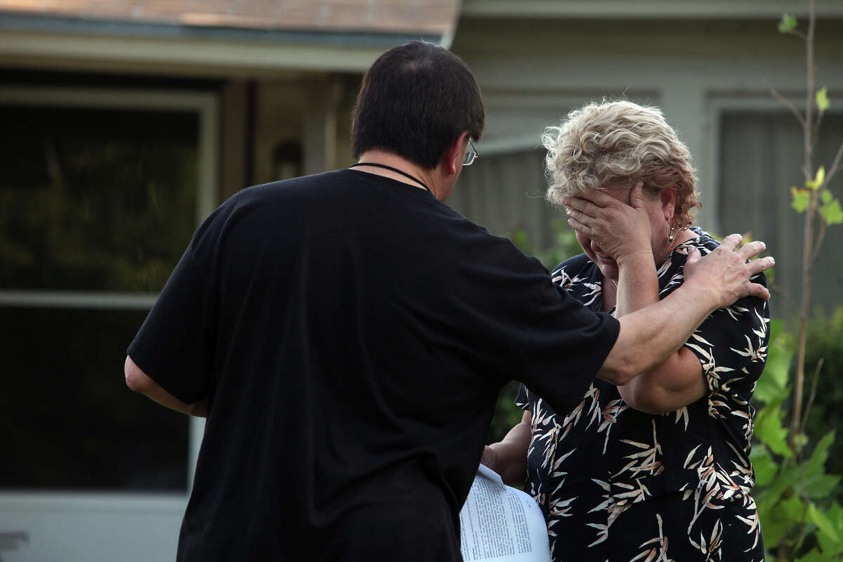 Nancy Murrah, right, the owner of the Amistad Residential Facility, breaks down in tears as she talks with Mario Resendiz, with the City of San Antonio Department of Human Services, outside the home in San Antonio on Saturday, August 18, 2012. Four men died in a fire at the facility Wednesday night.