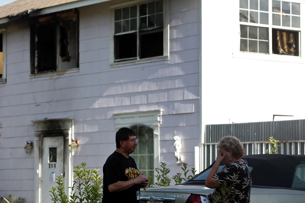 Nancy Murrah, right, the owner of the Amistad Residential Facility, talks with Mario Resendiz, with the City of San Antonio Department of Human Services, outside the home in San Antonio on Saturday, August 18, 2012. Four men died in a fire at the facility Wednesday night.