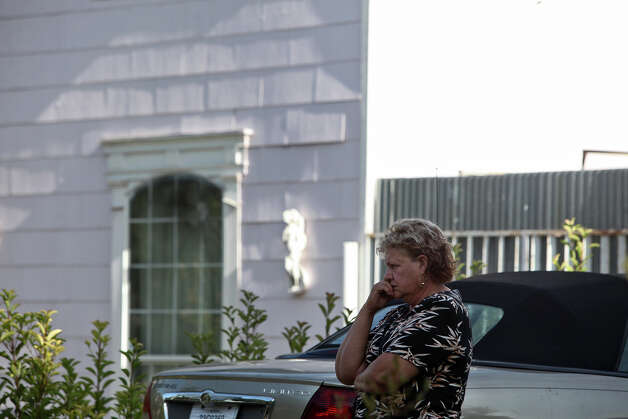 Nancy Murrah, the owner of the Amistad Residential Facility, stands by the home as she is visited by Mario Resendiz, with the City of San Antonio Department of Human Services, in San Antonio on Saturday, August 18, 2012. Four men died in a fire at the facility Wednesday night. Photo: Lisa Krantz, San Antonio Express-News / San Antonio Express-News