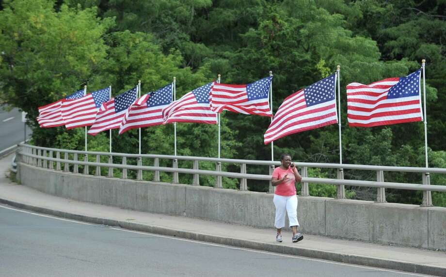 A woman talking on a cell phone walks past a group of American flags attached to the Post Road bridge over the MIanus River in Greenwich, Saturday afternoon, Aug. 18, 2012. Photo: Bob Luckey