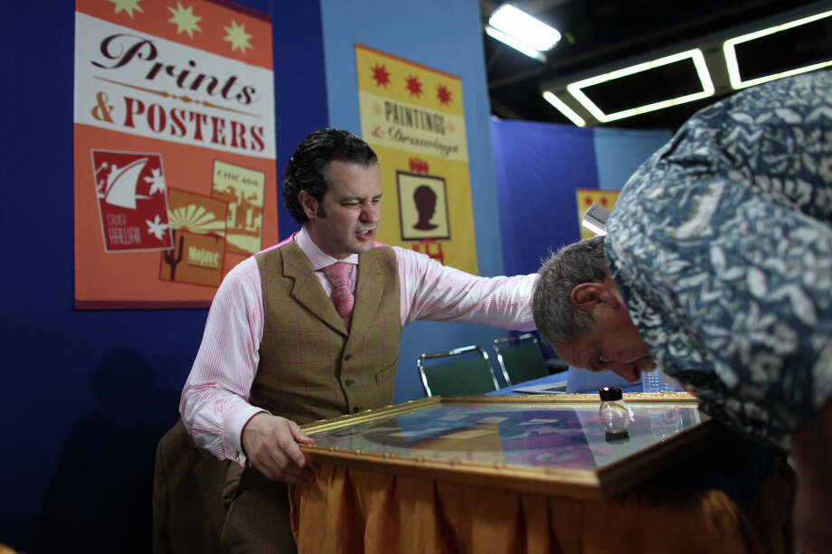 """Antiques Roadshow"" appraiser Nicholas Lowry breaks the bad news to Larry that his Rainier Beer poster is a reproduction of an original as the show visits Seattle's Washington State Trade and Convention Center on Saturday, Aug. 18, 2012. The popular PBS television show made a stop in Seattle during its summer tour. The show is scheduled to air beginning in January 2013 as part of its 17th season. More than 18,000 people applied for tickets to the show; only 3,000 were invited to the Saturday taping. Photo: JOSHUA TRUJILLO / SEATTLEPI.COM"
