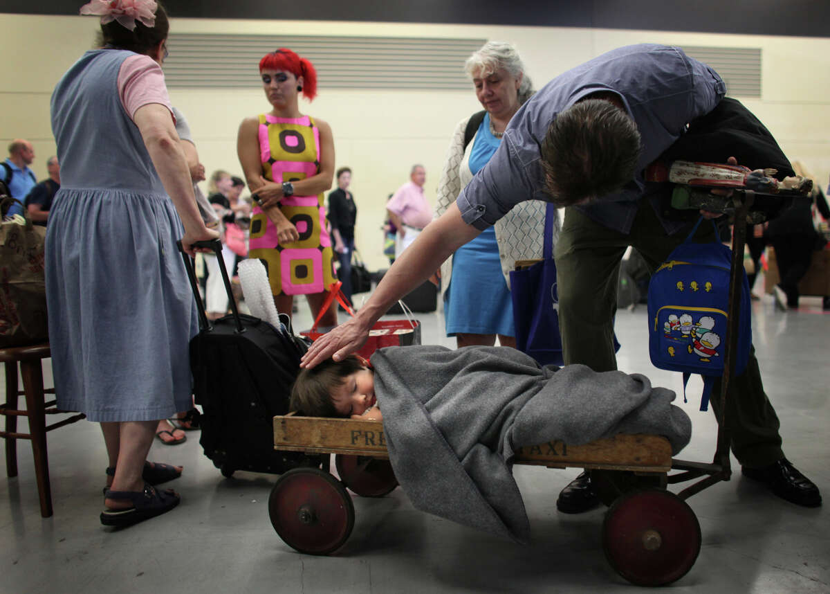Lewis, 3, rests in his 1920s 'Fresh Air Taxi' wagon as his dad Dan checks on his son while they wait in line for an appraisal. The wagon was found in the basement of a military officer's house at the Presidio in San Francisco and the family traveled to Seattle to be part of the show. They had been in line for about three hours before entering the set.