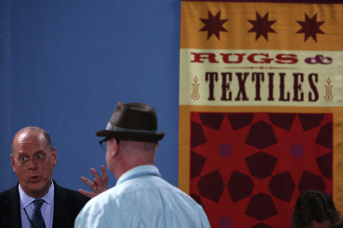 An appraiser explains the value of a rug to a guest.