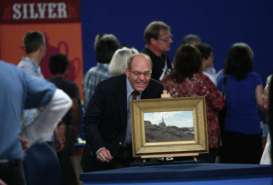 An appraiser looks over a painting on the set. Photo: JOSHUA TRUJILLO / SEATTLEPI.COM
