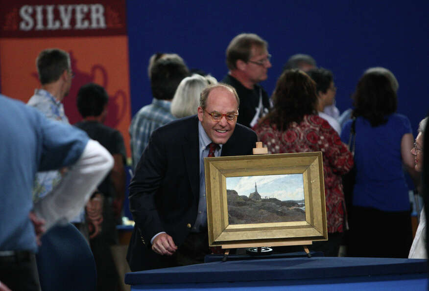 An appraiser looks over a painting on the set.