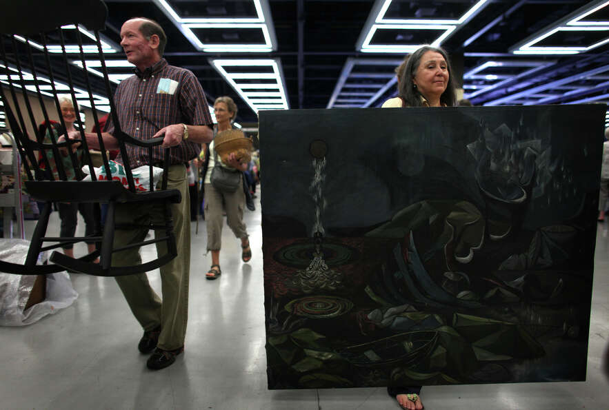 Teo, right, holds her Leo Kinney painting from 1946 while waiting in line.