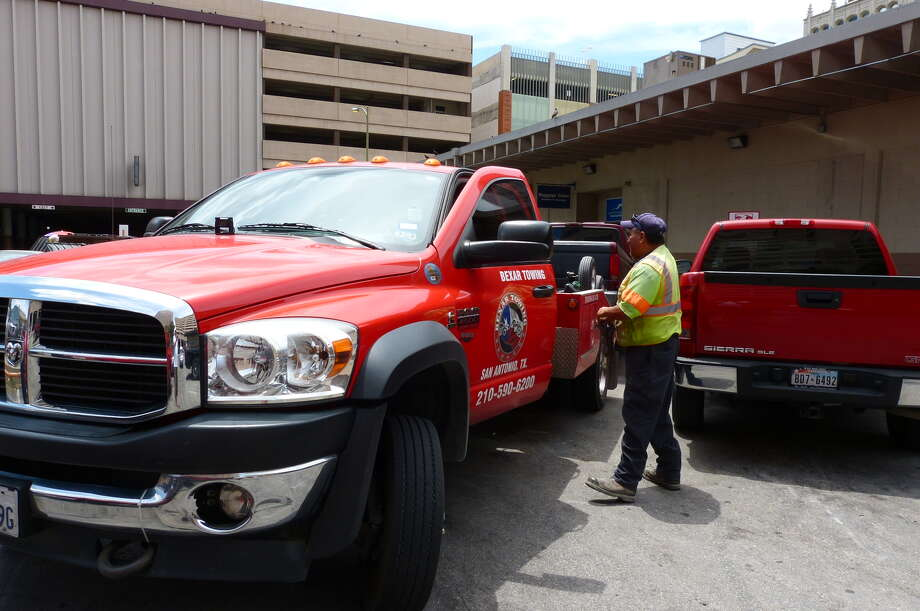 "A truck driver for Bexar Towing prepares to tow a Ford F-150 parked by Modesto Rodriguez at the downtown Greyhound bus station. The spot where Rodriguez parked was for shipping or receiving packages, not dropping off bus passengers. Rodriguez paid an $85 ""drop fee"" and got his truck back. The tow-truck driver declined to provide his name. Photo: San Antonio Express-News"