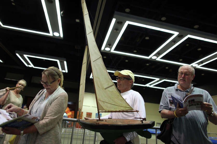 Bill holds a model sailboat while waiting in line.