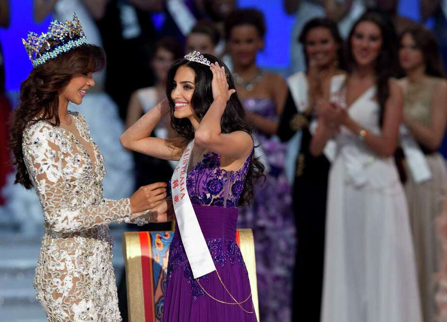 Runner-up Miss Australia Jessica Kahawaty, right, smiles after she was crowned by Miss World 2011 Ivian Lunasol Sarcos Colmenares of Venezuela. Photo: AP