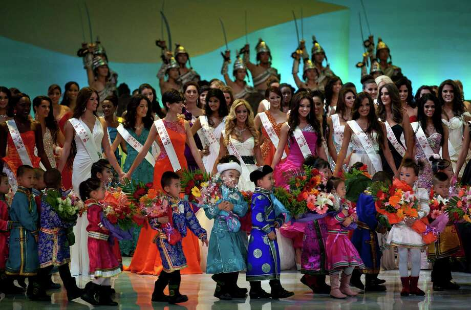 A group of children wearing Mongolia traditional costumes walk past Miss World contestants as they perform on stage. Photo: AP