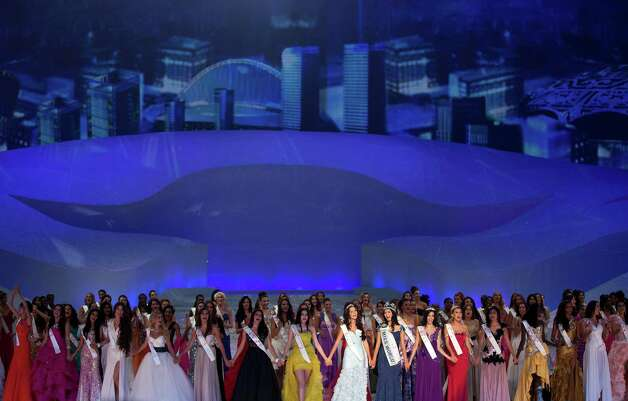 Miss World contestants hold hands and sing on stage. Photo: AP