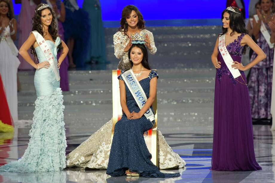 Miss World 2012 winner Yu Wenxia (center) of China receives the crown from previous winner Ivian Sarcos of Venezuela (top center) as second place contestent Miss Wales Sophie Moulds (left) and third place Miss Australia Jessica Kahawaty (right) watch. Photo: ED JONES, AFP/Getty Images / 2012 AFP