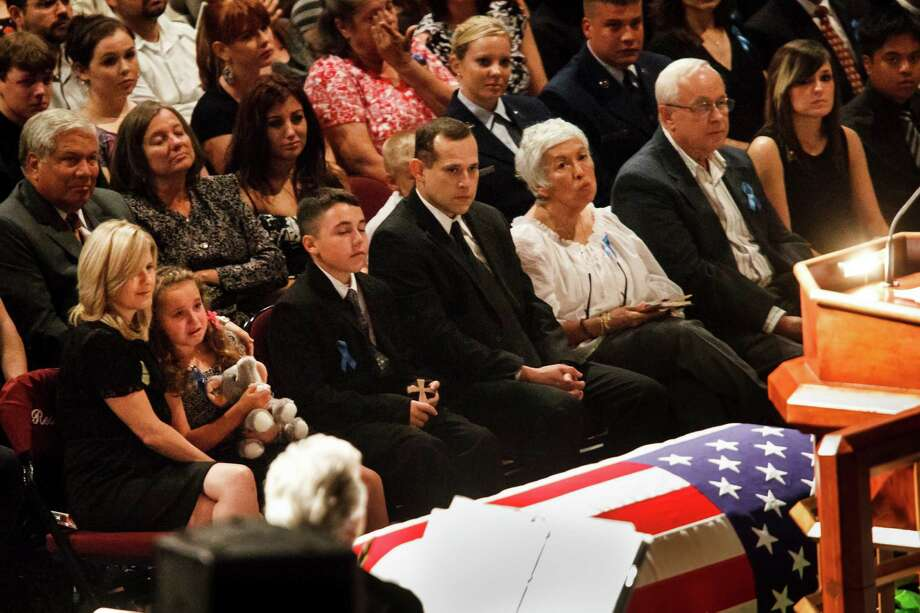 Donna Bachmann, left, comforts her daughter Caitlyn Bachmann, second from left, during the funeral service for her husband Brazos County Precinct 1 Constable Brian Bachmann at Reed Arena on the Texas A&M University Campus, Saturday, Aug. 18, 2012, in College Station.  Bachmann was fatally shot while serving an eviction notice to 35-year-old gunman Tres Caffall. Photo: Michael Paulsen, Houston Chronicle / © 2012 Houston Chronicle