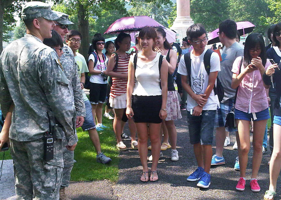 In this photo of Aug. 3, 2012, a tourist poses with cadets for a photo as others wait their turn during a tour of the U.S. Military Academy at West Point, N.Y.  Suburbs in the New York metropolitan area are stepping up their efforts to attract tourist dollars, not by competing with New York City, but by marketing themselves as complementary destinations. (AP Photo/Jim Fitzgerald) Photo: Jim Fitzgerald